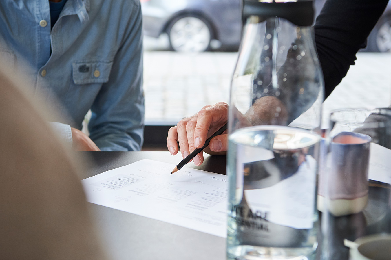 Detailfoto Arbeitssituation: Hand mit Stift skribbelt auf Papier